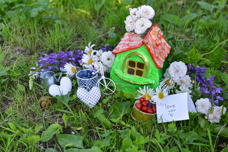 Small house with note love you, summer berries and flowers. Lovely miniature house for greeting cards, wedding or birthday concept, real estate, downsizing, home ownership. Vintage summer background Stock Photo