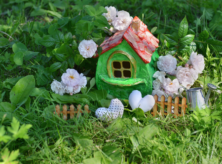 Small cute green house with roses, small fence, hearts and watering can in the garden. Miniature houses for greeting cards, wedding or birthday concept, real estate, downsizing, home ownership. Vintage summer background