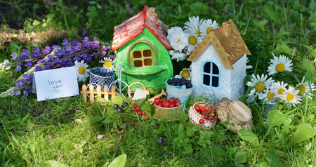 Two small houses with berry, flowers and text love you. Lovely miniature houses for greeting cards, wedding or birthday concept, real estate, downsizing, home ownership. Vintage summer background Stock Photo
