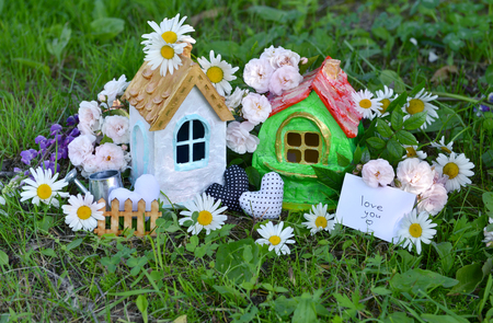 Toy houses with note and text love you, decorations, flowers in the grass. Lovely miniature houses for greeting cards, wedding or birthday concept, real estate, downsizing. Vintage summer background Stock Photo