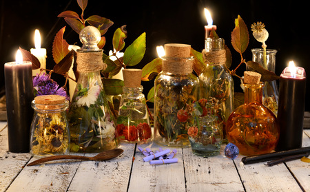Glass bottles with potions and herbs and black candle on witch table. Occult, esoteric, divination and wicca concept. Alternative medicine and homeopathic vintage background Stock Photo
