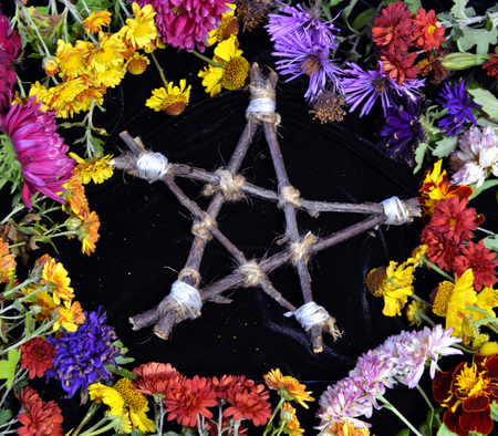 Hand made wooden pentagram in circle of flowers, top view. Occult, esoteric, divination and wicca concept. Halloween vintage background Stock Photo