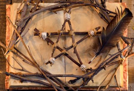 Houten pentagram, open boek en zwarte verenveer, bovenaanzicht. Occult, esoterisch, waarzeggerij en wicca-concept. Halloween vintage achtergrond Stockfoto