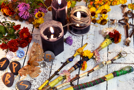 Magic wands, black candles, flowers and moth - death symbol, on witch table. Occult, esoteric, divination and wicca concept. Halloween vintage background
