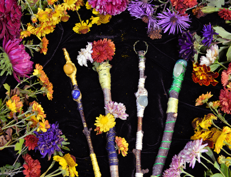 Decorated magic wands in circle of flowers, top view. Occult, esoteric, divination and wicca concept. Halloween vintage background