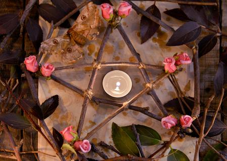 Pentagramme décoré en bois avec des feuilles, des fleurs et des bougies sur le papier, vue de dessus. Concept occulte, ésotérique, divination et wicca. Fond vintage d'Halloween