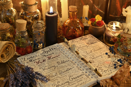 Magic book with spells, lavender bunch and black candle on witch table. Occult, esoteric, divination and wicca concept. Halloween vintage background