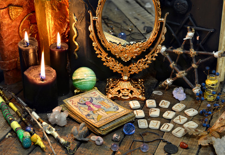 Tarot cards, magic wands, runes, black candles with mirror and old book. Occult, esoteric, divination and wicca concept. Mystic and vintage background Banco de Imagens