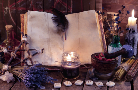 Witch book with pentagram, runes, magic objects and black candle. Occult, esoteric, divination and wicca concept. Mystic and vintage background Stok Fotoğraf