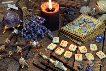 Tarot cards, ancient runes, black candle and pentagram. Occult, esoteric, divination and wicca concept. Mystic and vintage background Imagens