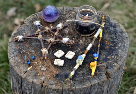 Magic wands, wooden pentagram, black candle and runes. Occult, esoteric, divination and wicca concept, mystic background
