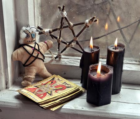 Muñeco vudú, cartas del tarot, pentagram y velas negras por la ventana vieja. Concepto oculto, esotérico, adivinación y wicca, fondo místico Foto de archivo