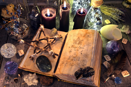 Old witch book with pentagram, black candles, crystals and ritual objects. Occult, esoteric, divination and wicca concept. Halloween background. No foreign text, all symbols on pages are fantasy, imaginary ones