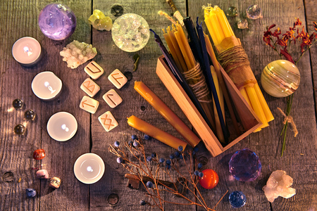 Ancient runes, candles, crystals, herbs and magic ritual objects on planks. Occult, esoteric, divination and wicca concept. Halloween background with vintage objects