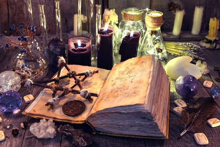 Open book with black magic spells, pentagram, ritual objects and candles on witch table. Occult, esoteric, divination and wicca concept. Halloween background. No foreign text, all symbols on pages are fantasy, imaginary ones Stock Photo