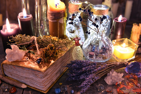 Witch ritual collection with old spelling book, lavender, bottles, herbs and magic objects. Occult, esoteric, divination and wicca concept. Halloween background with vintage objects Stockfoto