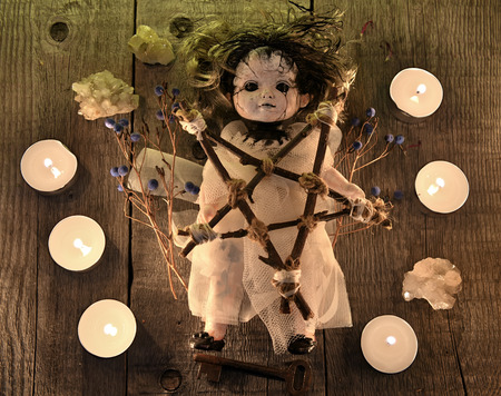 Scary voodoo doll with candles, pentagram and poison berries on witch table. Occult, esoteric, divination and wicca concept. Halloween background with vintage objects Фото со стока - 95154909