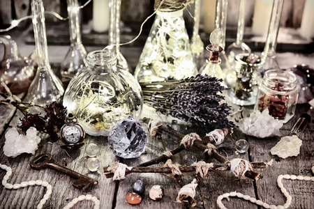 Magic bottles with lights, pentagram, crystal, lavender flowers and ritual objects on witch table. Halloween, occult, esoteric and wicca concept. Vintage background