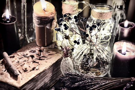 Evil book with black candles, glass bottles, poison berries and herbs on witch table. Halloween, occult, esoteric and wicca concept. Vintage background