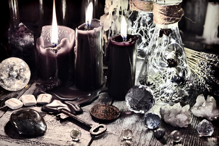 Black candles, crystals and stones, ancient runes, key and ritual bottles on witch table. Halloween, occult, esoteric and wicca concept. Vintage background