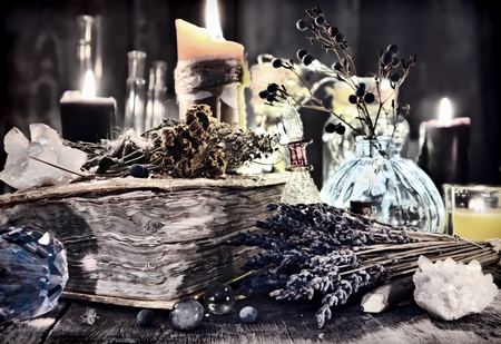 Antique witch book with lavender flowers, magic ritual objects, healing herbs, crystal and black candles. Halloween, occult, esoteric and wicca concept. Vintage background