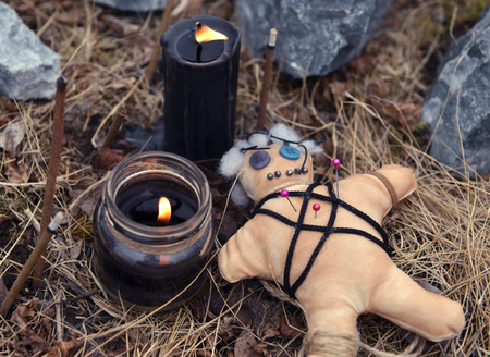Voodoo doll with burning black candles and incense sticks among stones. Mystic background with ritual esoteric objects, occult and halloween concept Stock Photo