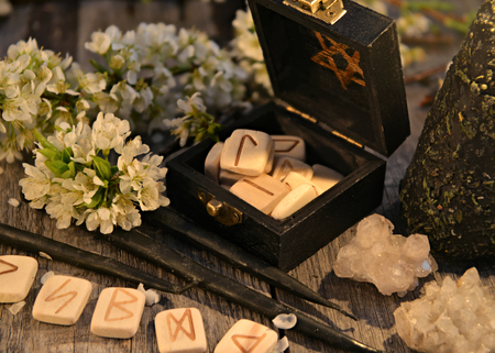 Close up with runes, crystals, white flowers and black candles. Occult, esoteric and divination still life. Halloween background with vintage objects Foto de archivo
