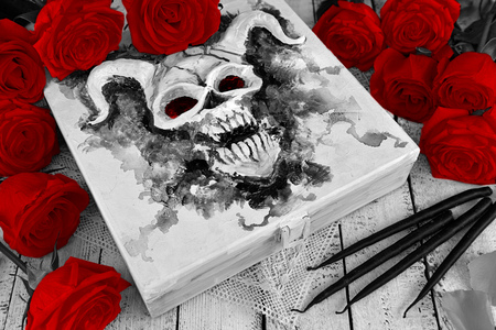 Box with evil diabolic monster on the cover, black candles and red roses. Vintage mystic background, esoteric and occult Halloween concept