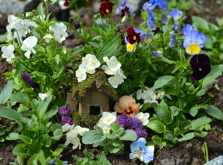 Small fairy house in viola flowerbed. Lovely miniature house for greeting cards, wedding or birthday concept, real estate, downsizing, home ownership. Vintage summer background