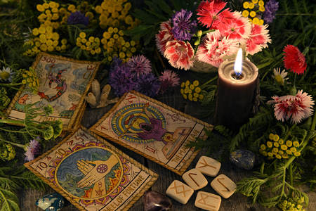 Still life with old tarot cards, black candle, runes, healing herbs and flowers. Mystic background with ritual esoteric objects, occult, fortune telling and halloween concept Фото со стока - 107341012