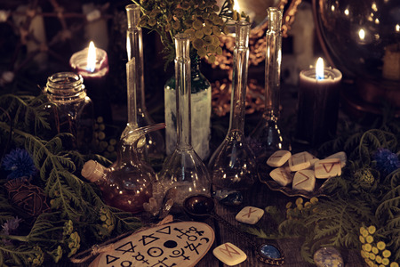 Still life with alchemy ritual objects, old bottles, herbs and black candles. Mystic background with ritual esoteric objects, occult, fortune telling and halloween concept Banco de Imagens