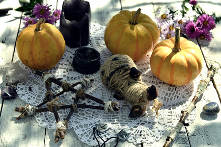 Voodoo doll with pumpkins, pentagram and black candles on lace napkin. Mystic background with ritual objects, occult, fortune telling and halloween concept Фото со стока