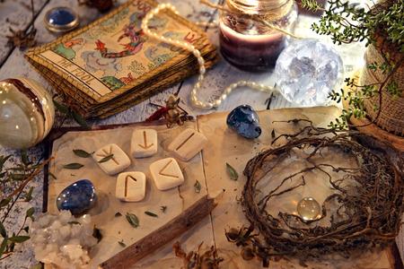 Open dagboekboek met runen, gedroogde kruiden en tarotkaarten op tafel. Magisch gotisch ritueel. Wicca, esoterische en occulte achtergrond met vintage objecten