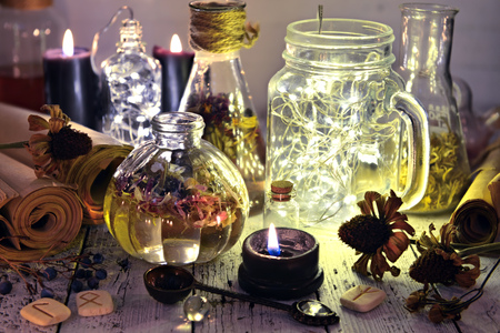 Still life with luminous bottles, paper scrolls, runes, seeds and black candle. Magic gothic ritual. Wicca, esoteric and occult background with vintage objects