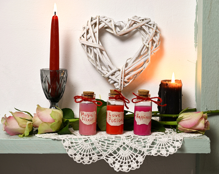 Red and black candles, roses, heart symbols, bottles with magic elixir, love potion, happiness. Magic wicca concept, witch rite. Romantic vintage valentine's day and wedding background