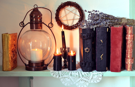 Witch shelf with magic books, old lamp, black candles and lavender herbs. Magic gothic ritual. Wicca, esoteric, divination and occult background with vintage objects