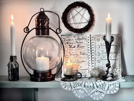 Open book diary lunar phases, burning candles, pentagram and old lamp on shelf. Magic gothic ritual. Wicca, esoteric, divination and occult background with vintage objects Archivio Fotografico