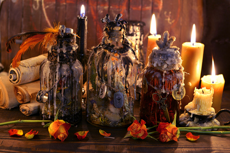 Witch vintage bottles with candles and ancient paper scrolls. Wicca, esoteric, Halloween and occult background with vintage magic objects for mystic rituals Banco de Imagens