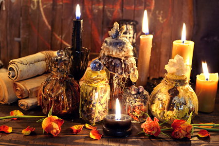 Witch bottles, black candles and roses again planks with pentagram. Wicca, esoteric, Halloween and occult background with vintage magic objects for mystic rituals