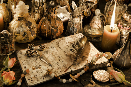 Magic ritual bottles with open witch book, quill and cross in candlelight on the table. Wicca, esoteric and Halloween background. No foreign text, all symbols on pages are fictional. Banco de Imagens