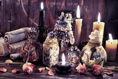 Antique parchments with magic witch bottles and burning candles. Wicca, esoteric, Halloween and occult background with vintage magic objects for mystic rituals Banco de Imagens
