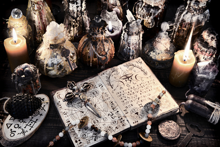 Open magic book with ancient symbols, witch bottles and black candles. Halloween, esoteric and occult background. No foreign text, all symbols on pages are fictional.