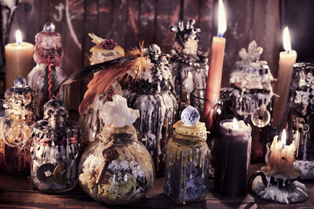 Witch bottles and candles in magic candlelight on the table. Wicca, esoteric, Halloween and occult background with vintage magic objects for mystic rituals