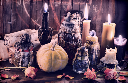 Witch bottles with pumpkin, black candles and paper scrolls. Wicca, esoteric, Halloween and occult background with vintage magic objects for mystic rituals