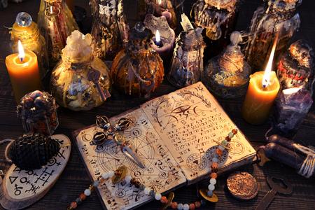 Libro de brujas antiguo con hechizo mágico, velas negras y botellas decoradas. Halloween, fondo esotérico y oculto. Sin texto extranjero, todos los símbolos de las páginas son ficticios.