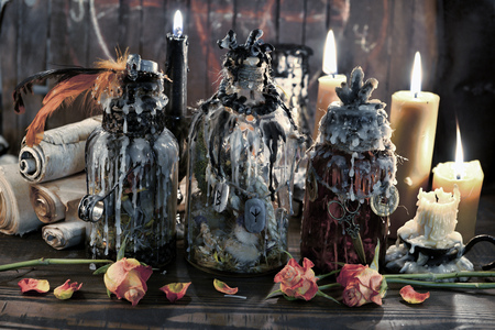 Magic bottles with burning candles, scrolls and flowers on witch table. Wicca, esoteric, Halloween and occult background with vintage magic objects for mystic rituals Banco de Imagens