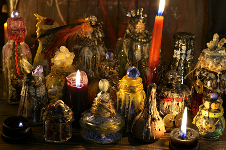 Magic decorated bottles with burning candles on the witch table. Wicca, esoteric, Halloween and occult background with vintage magic objects for mystic rituals Banco de Imagens