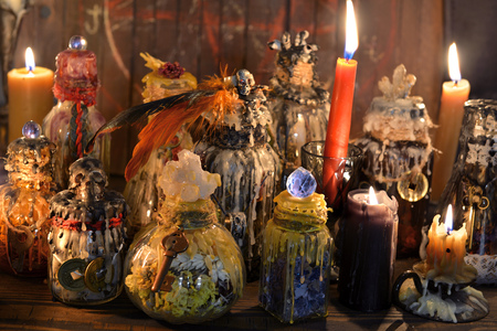 Witch laboratory with alchemy magic bottles in candlelight. Wicca, esoteric, Halloween and occult background with vintage magic objects for mystic rituals