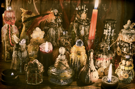 Witch table with decorated magic bottles and burning candles. Wicca, esoteric, Halloween and occult background with vintage magic objects for mystic rituals Banco de Imagens