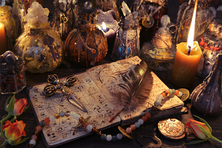 Witch book with cross, quill, burning candles and magic bottles on the table. Wicca, Halloween and occult background. No foreign text, all symbols on pages are fictional.